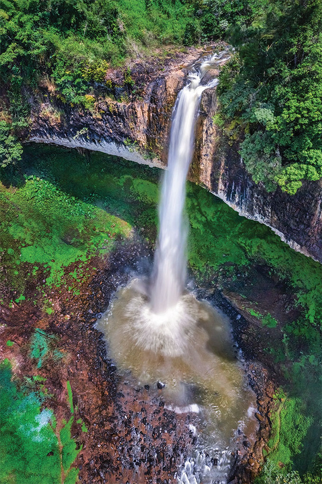 Descending over high cliffs, the dynamic Lieng Nung Waterfall in Dak Nong province is surrounded by the lush green of the jungle.