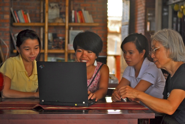 Ms Reiko Usuda with U Cafe staff are using a laptop donated by an NGO